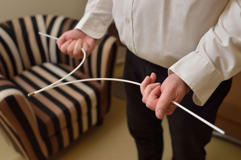 at-home Experte bei der Messung mit einer Wünschelrute